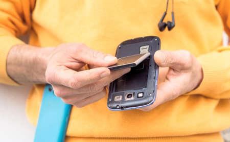 男の手の挿入携帯電話バッテリー屋外で立って - モバイル コンポーネントを置き換える男性を電話の下の部分を中心に画像を閉じる