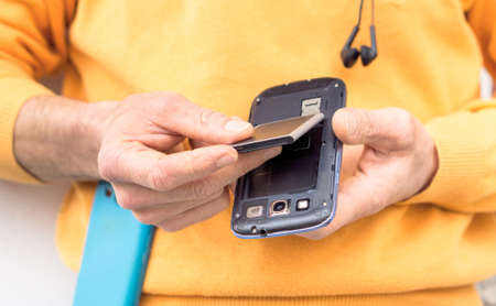 Man hands inserting mobile phone battery standing outdoors - Male replacing mobile component close up image with main focus on telephone lower part
