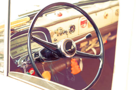 Vintage car steering wheel and dashboard cabin view - Classic automobile interior side angle image - Concept of old style  vehicle technology with sepia filter look Banco de Imagens