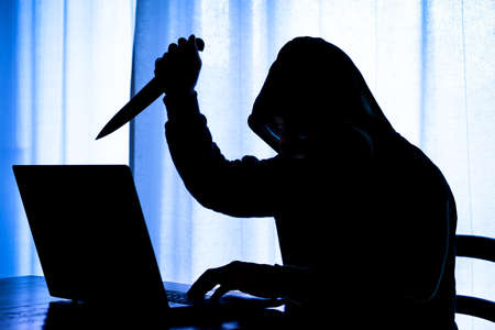 Hooded dark man at pc brandishing knife with a threatening attitude - Dangerous cyber stalker holding sharp blade at laptop in the darkness - Concept of internet harassment with focus on evil face Stock Photo