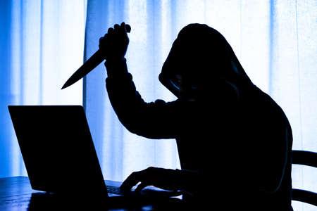 Pc 振り回して威嚇的な態度 - ナイフでフード付きの暗い男危険なサイバー ストーカー持株シャープ ノート パソコンでブレード闇に悪の顔にフォー