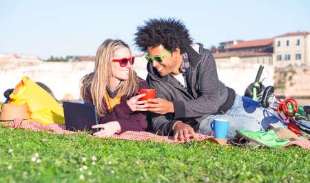 중간 계절 의류 - 아프리카의 머리 남자와 금발여자가 서로 찾고 화창한 주말 하루에 웃는 차 컵을 들고 공원에서 잔디에 누워 커피를 마시는 젊은 inter 스톡 콘텐츠