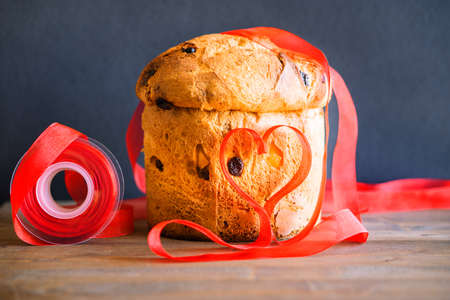 Panettone Christmas gift preparation with red ribbon heart - Traditional italian winter holidays bakery