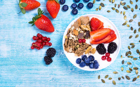 Breakfast  fruit bowl with yogurt ,strawberries , blueberries , blackberries , cranberry and assorted cereals flat lay top view - Healthy nutrition concept on vintage blue wood background with seeds Stockfoto
