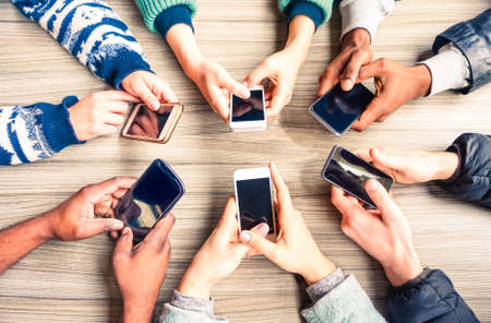 Hands circle using phones on table top view - Multiracial people holding mobile devices sitting around at office desk - Concept of friends team working and modern communication technology above image 스톡 콘텐츠