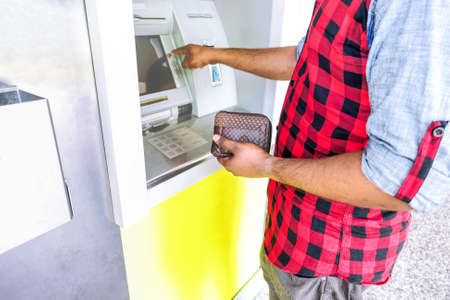 Man withdrawing money at atm machine is holding wallet and selecting bank service - Concept of everyday life , daily expenses , costumer banking , transaction system