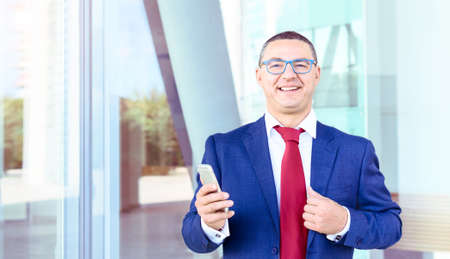 Confident business man smiling looking at camera and holding mobile phone - Well dressed manager positive attitude standing on modern financial building  background - Before a work meeting  concept