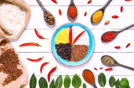Different types of rice  surrounded by variety of aromatic spices top view image on white wood background - Concept of lunch time clock with colorful  ingredients on happy kitchen table