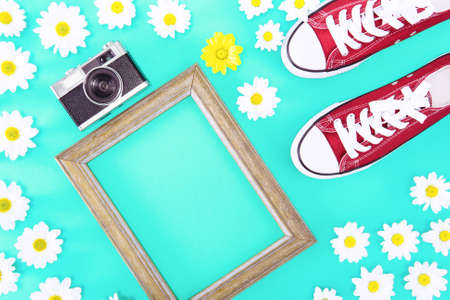 Floral spring frame with flat lay top view - Springtime concept with copy space surrounded by vintage camera with red sneakers and daisies flowers on turquoise background