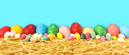 Row of  Easter eggs on straw with blue cyan background -  Rustic spring holiday banner with traditional  symbolic food and large copy space