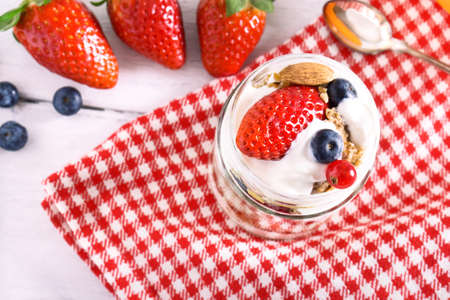 Yogurt parfait with strawberry and cereal top view - Fruit dessert from above - Healthy spring  breakfast concept over red table cloth background