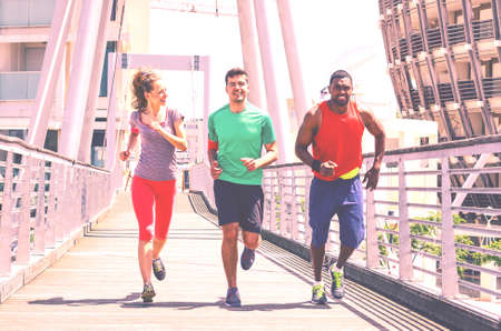 Multiethnic runners on urban background - Group of multiracial friends jogging in city at spring time - Young sporty people running together outdoors  - Concept of healthy lifestyle  matte filter look