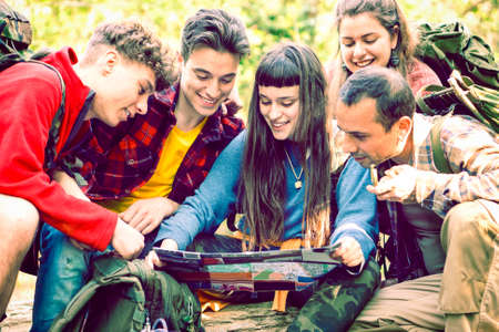 Hiking group of happy friends looking at map sitting  in the  forest outdoors - Teenagers excursion team planning tour outdoors - Concept of  trekking , teamwork , teenage friendship - Vintage filter