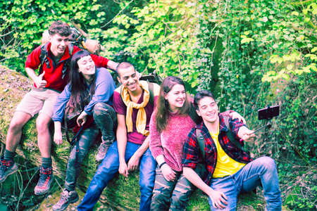Multiracial group of young friends hikers taking selfie at national park on forest background - Row of teenagers having fun using mobile phone technology outdoors into the wild - Adventure concept