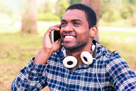Afro male phone calling outdoors - Happy african american man holding mobile  outside in the park - Cheerful student with headphones casual style using smartphone on green background at day time