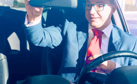 Elegant driver looking at rear view mirror before a business appointment - Businessman straightening his tie inside car at morning sun light - Concept of taking care of last details for dating or trip
