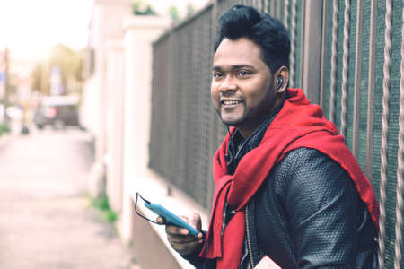 Young indian guy with headsets listening music holding mobile phone outdoors - Handsome bangladeshi man using mobile technology standing in city street looking ahead and smiling - Soft matte filter