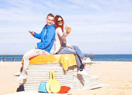 Happy young couple taking selfie back to back on the beach - Teenagers using mobile phone camera are relaxing on sunny spring day outdoors - Seasonal concept of lifestyle and technology addiction