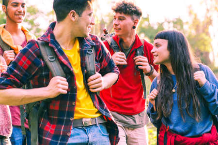Happy young friends hiking with positive attitude - Cheerful group of teenagers smiling looking at each other holding trek backpack - Concept of friendship, travel and outdoor activity - Focus on girl Stock Photo
