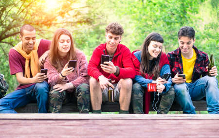 Group of young friends in a row holding mobile phone looking down smiling - Happy teenagers on hiking clothing  sitting outdoor using smartphone - Concept of teens friendship , technology addiction