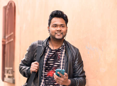 Young indian man holding mobile phone with earphones is walking  confident - Happy asian male using smartphone smiling and looking ahead - Concept of lifestyle  and tecnology with pink wall copy space Stock Photo