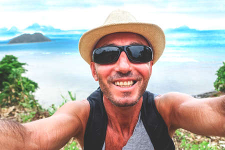 Happy man taking selfie on summer trekking day at Palawan island - Cheerful traveler self photo on blue ocean background - Concept of travel around world and outdoor activities - Soft vintage filter