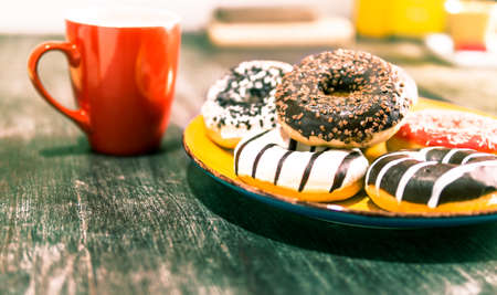 Assorted donuts and red coffee cup on old  wooden table - Doughnuts on yellow plate with tea background - Concept of unhealthy nutrition wth tasty food at breakfast time - Shallow depth of field Stock Photo