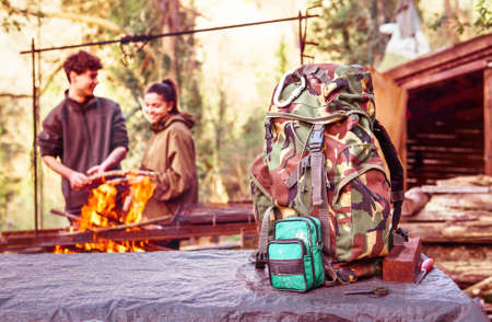 Hiker military backpack with happy friends preparing fire on background - Cheerful couple on trekking trip setting barbeque at camping site with  rucksack foreground - Concept of outdoor equipment