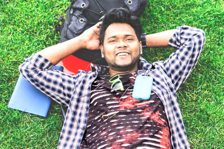 Young indian man daydreaming at park listening music by phone with dreamy facial expression - Happy bengali male relaxing on grass top view - Concept of relax, peace, break time - Matte filter look Stock Photo