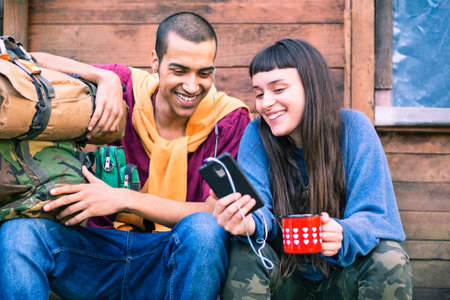 Interracial couple of young hikers looking at phone holding coffee - Happy teens on trekking outfit using smartphone sitting outdoor - Pretty girl showing video at friend - Mobile technology concept Stock Photo