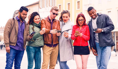 Multicultural group of friends looking  phone with surprised face - Multiracial teenagers having fun using smartphone standing in the street at winter - Concept of addiction to modern technology