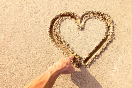 Heart shape on sand drawn down by man hand at the beach top view image with copy space - Concept of travel , love , health