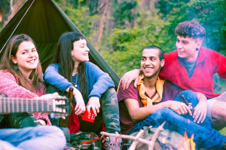 Group of multiracial friends camping around fire drinking together - Happy multicultural teenagers having fun sitting at campfire playing music and smiling - Concept of outdoor activity and friendship