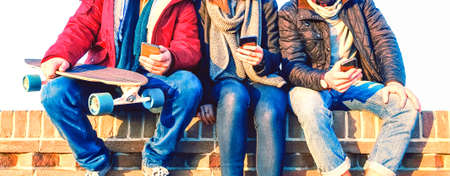 Group of friends using mobile phone sitting in row at winter time - Young people texting on smartphone - Teenagers holding cellphone outdoor -  Cropped image of teens addicted to modern technology