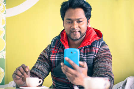 Young indian man messaging with phone and  stirring coffee sitting at bar cafe - Handsome bangladeshi happy guy holding mobile on green background - Social media addiction concept with copy space