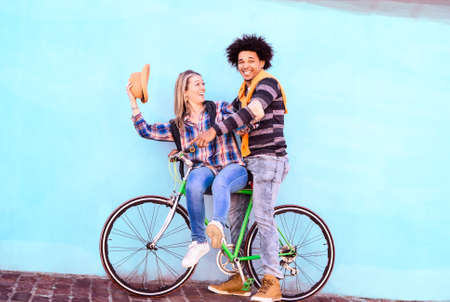 Happy interracial couple riding sport bike on blue sky wall background - Playful friends on bicycle tour having fun moments together - Concept of healthy lifestyle and travel in tilted composition