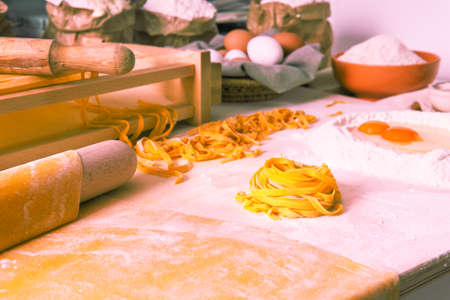 Handmade tagliatelle noodle angle view of rustic kitchen tools and all ingredients  - Fresh italian pasta hand made regional specialty - Concept of traditional healthy  food Stock Photo