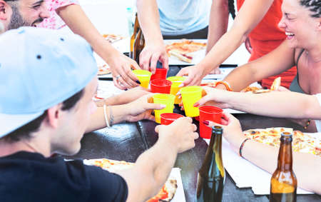 Happy friends toasting at pizza party day outdoor -  Young people hands circle holding drinks and laughing around table - Concept of joy , friendship , togetherness - Focus on plastic glasses - Image