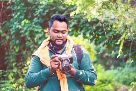Young indian tourist man holding camera on green woods background - Portrait of handsome asian photographer in forest excursion looking down at vintage device - Concept of travel, nature, hiking, trek Banco de Imagens