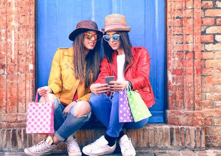 Trendy clothing women looking mobile phone holding shoppers sitting outside house - Young female hipsters using smartphone relax after shopping day - Concept of consumer society and modern technology