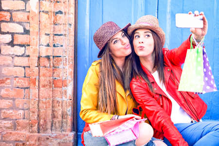 Best friends women taking selfie in funny faces holding shoppers wearing trendy fashion clothes - Girls having fun using phone camera sitting outside on old wall background - Female friendship concept Banco de Imagens