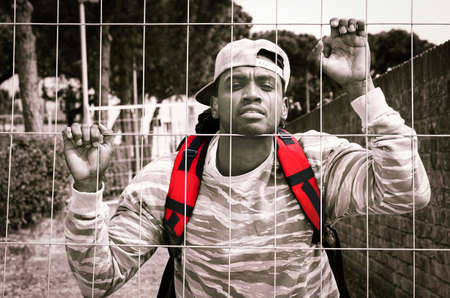 African american man bihind wire mesh looking at camera with sad facial expression - Young refugee male holding metal fence - Concept of barriers to freedom ,  with dramatic black and white filter and highlighted red colors - Image Banco de Imagens