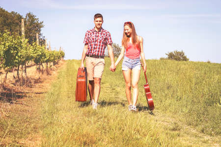 Happy young couple walking in a field holding hands carrying suitcase and guitar on sunny summer day - Lovers on country path   - Romantic concept of love and travel - Nostalgic filter look image Banco de Imagens