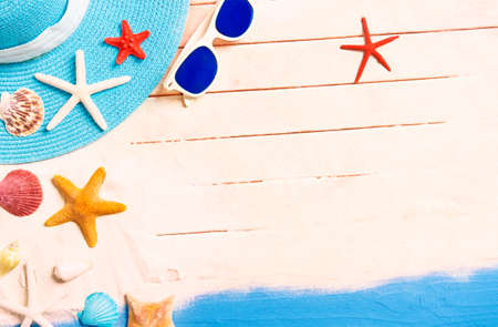 Summer holidays background with starfish and beach accessories -  Conceptual frame of summertime vacation with blue hat , sunglasses and shells on tropical white sand - Top view image with copy space Banco de Imagens