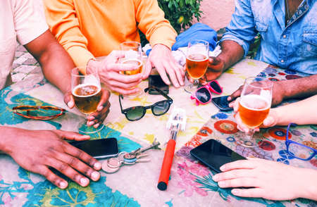Group of multiracial friends drinking beer at cafe with mobile phones and glasses on table - Young people together having a drink break time in outdoor bar on summer day - Main focus on top Image Banco de Imagens