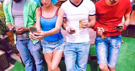 Gruppo di amici che utilizzano il telefono cellulare tenendo la birra in piedi all'aperto alla festa estiva con barbecue - Giovani tifosi di calcio che utilizzano smartphone e bevono nel giardino del bar in una giornata di primavera - Concetto di tecnologia - Immagine Archivio Fotografico