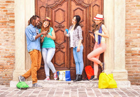 Multiracial friends using mobile phone standing outdoor - Group of happy teenage looking cellphone in the city - Travel and technology concept - Image