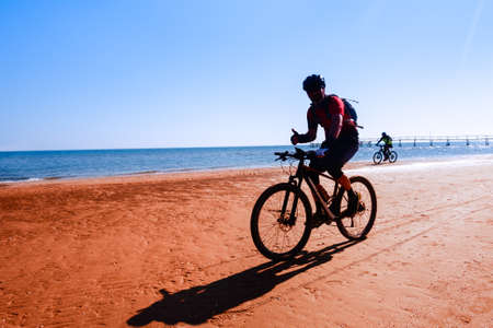 Man cycling on sport bike showing thumb up on ocean background - Silhouette of people riding bicycle on the beach shore with morning backlight - Lifestyle concept of healthy holiday activity - image Stock fotó