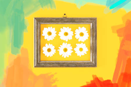 Daisies in wooden frame surraunded by brush strokes of color paint trends on  yellow interior wall background - Colorful spring concept with trendy pastel colour tones - Image Stock Photo