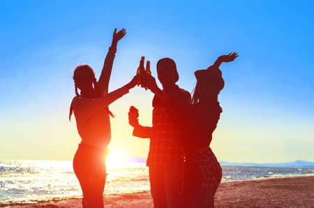 Silhouette of happy friends dance at beach party on sunrise  light - Teenagers cheers with beer bottles having fun  moment on summer holiday - Concept of teenage friendship - Soft bluish filter image Stock fotó